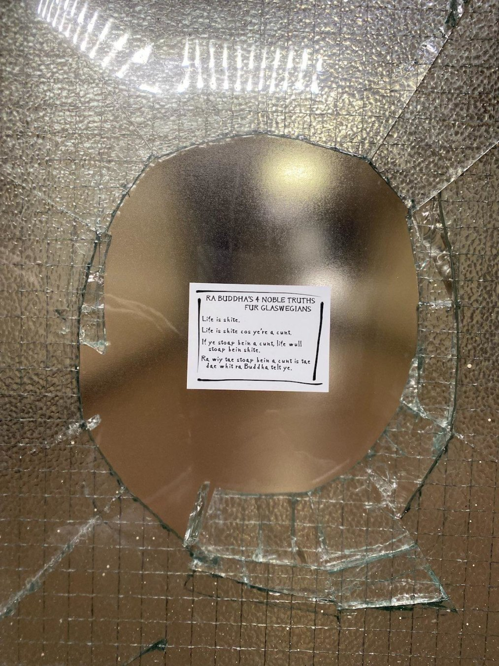 Broken glass panel in a block of flats, covered with a sticker with the Buddha's 4 Noble Truths in Glaswegian Scots